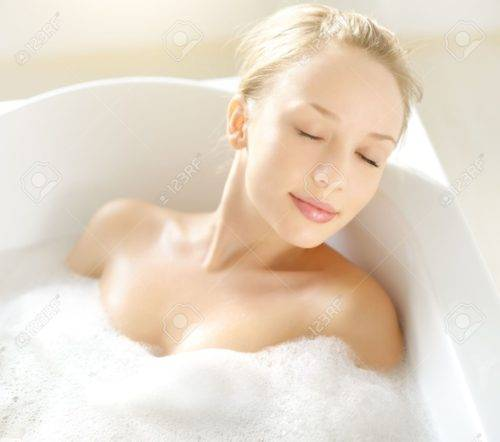 17803567-Attractive-girl-relaxing-in-bath-on-light-background-Stock-Photo